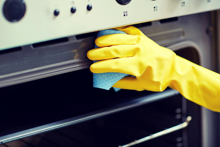 dirty: people, housework and housekeeping concept - close up of woman hand in protective glove with rag cleaning oven at home kitchen