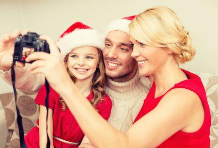 familia, la navidad, Navidad, la felicidad y el concepto de la gente - sonriendo familia en Santa helper sombreros tomar la fotografía con cámara de fotos