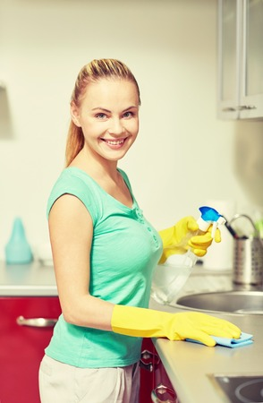 cleanser: people, housework and housekeeping concept - happy woman in protective gloves cleaning table with rag and cleanser at home kitchen