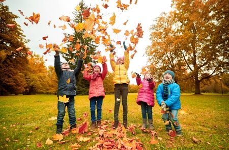 kids playing: childhood, leisure, friendship and people concept - group of happy kids playing with autumn maple leaves and having fun in park
