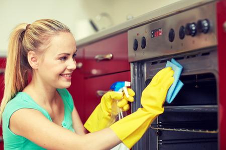 사람, 집안일과 청소 개념 - 집 부엌에서 스프레이 세제 세척 오븐의 병 행복한 여자