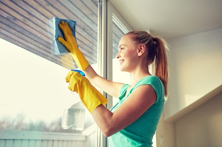 cleaning window: people, housework and housekeeping concept - happy woman in gloves cleaning window with rag and cleanser spray at home Stock Photo