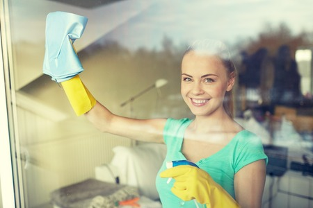 people, housework and housekeeping concept - happy woman in gloves cleaning window with rag and cleanser spray at home Banque d'images