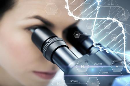 la ciencia, la química, la tecnología, la biología y la gente concepto - cerca de la mujer de ciencias mirando al microscopio en el laboratorio clínico sobre la fórmula química de hidrógeno y estructura de la molécula de ADN Foto de archivo