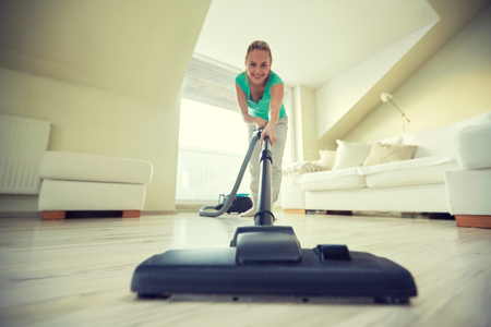 cleaner: people, housework and housekeeping concept - happy woman with vacuum cleaner at home