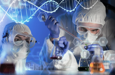 discovering: science, chemistry, biology, medicine and people concept - close up of scientists with pipette and flasks making test in clinical laboratory over hydrogen chemical formula and dna molecule structure Stock Photo