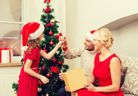 decorate: family, christmas, x-mas, happiness and people concept - smiling family in santa helper hats decorating christmas tree Stock Photo
