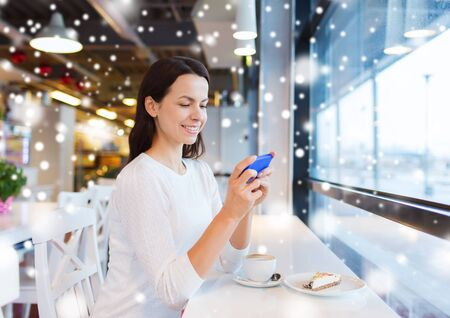mobile sms: drinks, food, people, technology and lifestyle concept - smiling young woman with smartphone drinking coffee at cafe over snow effect Stock Photo