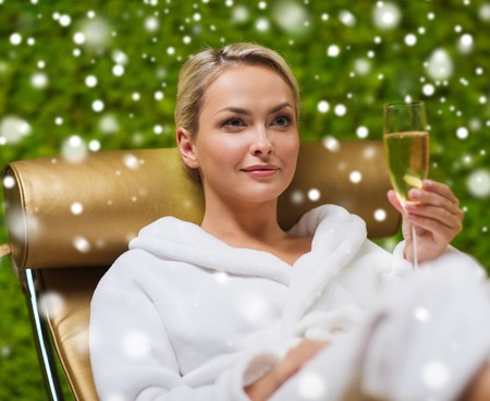 winter holiday: people, beauty, lifestyle, holidays and relaxation concept - beautiful young woman in white bath robe lying on chaise-longue and drinking champagne at spa with snow effect