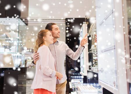 shopping malls: sale, consumerism and people concept - happy couple pointing finger to shopping window at jewelry store in mall with snow effect