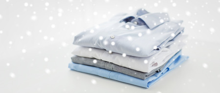 ironed: ironing, laundry, clothes, housekeeping and objects concept - close up of ironed and folded shirts on table at home over snow effect
