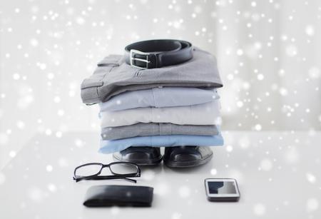 stile: affari, stile, vestiti e oggetti concetto - stretta di abiti maschili formali e cose personali sul tavolo a casa su effetto neve
