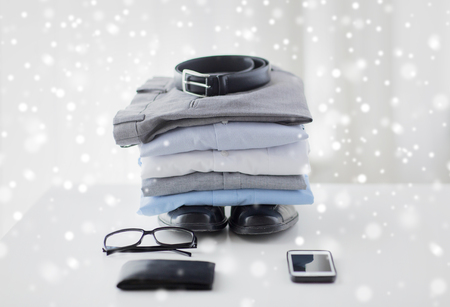 life style: business, style, clothes and objects concept - close up of formal male clothes and personal stuff on table at home over snow effect Stock Photo