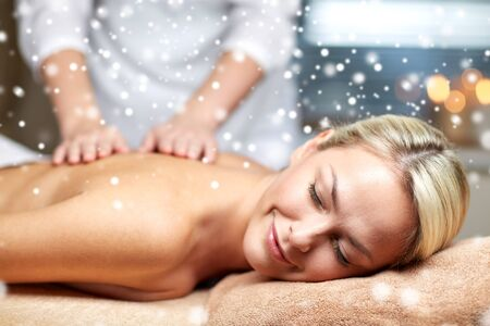 massage: les gens, la beaut�, spa, hiver et relaxation concept - close up de la belle jeune femme allong�e avec les yeux ferm�s et ayant la main massage du dos dans le spa salon avec effet de neige