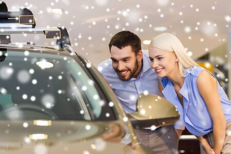 concept car: auto business, car sale, consumerism and people concept - happy couple buying car in auto show or salon over snow effect
