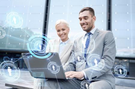 ビジネス、コミュニケーション、技術、人々 のコンセプト - ラップトップ コンピューターとネットワークの投影と街のビジネスマンの笑みを浮かべ 写真素材