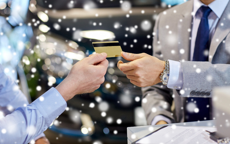 credit cards: auto business, sale and people concept - close up of customer giving credit card to car dealer in auto show or salon over snow effect Stock Photo