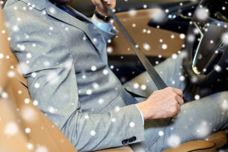 fastening: safety, driving and people concept - close up of man in elegant business suit fastening seat safety belt in car over snow effect