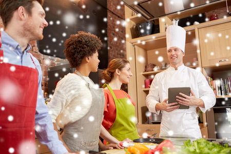 food technology: cooking class, culinary, food, technology and people concept - happy friends with tablet pc in kitchen over snow effect