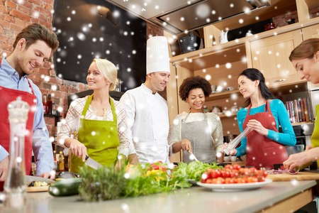 cooking class, culinary, food and people concept - happy group of friends with male chef cook cooking and talking in kitchen over snow effect