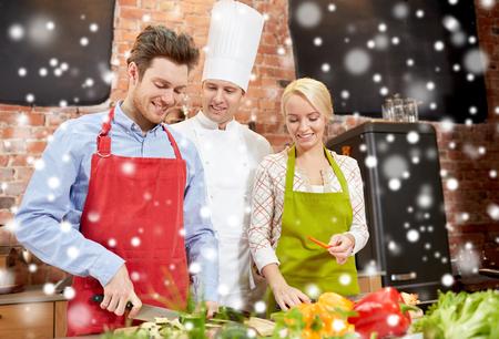 kulinarne: Klasa gotowanie, kulinarne, jedzenie i ludzie koncepcja - szczęśliwa para i mężczyzn kucharz kucharz w kuchni na efekt śniegu Zdjęcie Seryjne