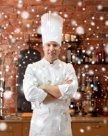 christmas cooking: cooking and people concept - happy male chef cook with crossed hands in restaurant kitchen over snow effect