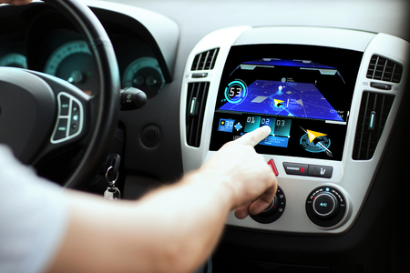 navegacion: transporte, destino, la tecnología moderna y la gente concepto - mano masculina en busca de ruta utilizando el sistema de navegación en pantalla salpicadero de un coche Foto de archivo