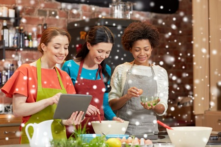 food technology: cooking class, friendship, food, technology and people concept - happy women with tablet pc computer in kitchen over snow effect