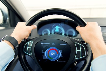 private parts: transport, business trip, technology and people concept - close up of male hands holding car wheel and driving with volume level icon on board computer screen