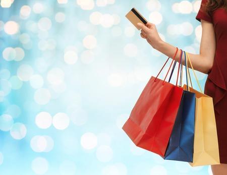 Konzept Menschen, Verkauf und Konsum - Nahaufnahme von Frau mit Einkaufstüten und Bank- oder Kreditkarte über blau Urlaub Lichter Hintergrund
