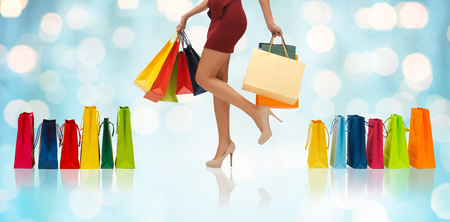 short skirt: people, sale and consumerism concept - close up of woman in red short skirt and high heeled shoes with shopping bags over blue holidays lights background Stock Photo