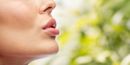 kunststoff: Schönheit, Leute, Make-up und plastische Chirurgie Konzept - Nahaufnahme der jungen Frau Lippen über grüne natürlichen Hintergrund