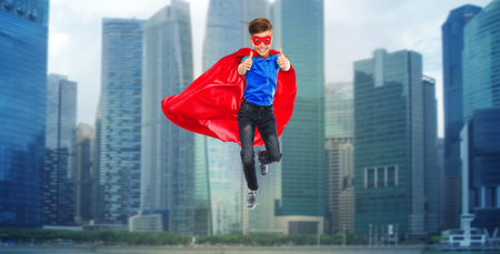 air movement: happiness, freedom, childhood, movement and people concept - boy in red super hero cape and mask flying in air and showing thumbs up