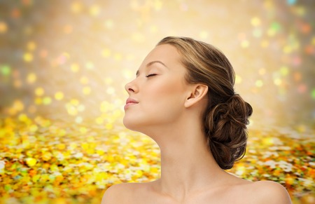 beauty eyes: beauty, people and health concept - young woman face with closed eyes and shoulders side view over golden holidays lights or yellow glitter background