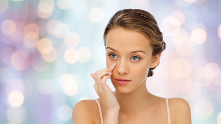 eye cream: beauty, people, cosmetics, skincare and health concept - young woman applying cream to her face over purple holidays lights background