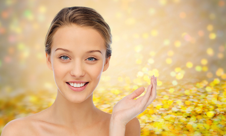 smiling face: beauty, people and health concept - smiling young woman face and shoulders over golden glitter or holidays lights background