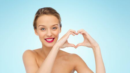 people teenagers: beauty, people, love, valentines day and make up concept - smiling young woman with pink lipstick on lips showing heart shape hand sign over blue background Stock Photo