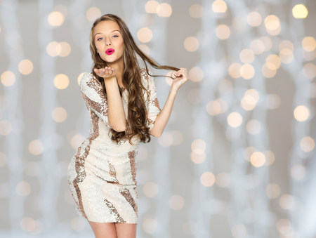 blow: people, style, holidays, hairstyle and fashion concept - happy young woman or teen girl in fancy dress with sequins and long wavy hair sending blow kiss over lights background