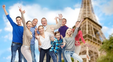 mid teens: family, travel, tourism and people concept - group of happy men, women and boy having fun and waving hands over eiffel tower background