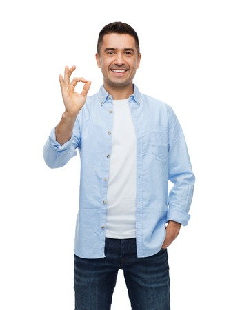 happiness, gesture and people concept - smiling man showing ok hand sign Stock Photo
