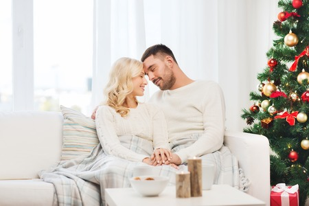 cuddling: family, christmas, holidays, love and people concept - happy couple covered with plaid sitting on sofa at home
