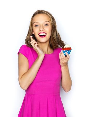 jovenes felices: gente, días de fiesta, fiesta, comida chatarra y celebración concepto - mujer joven feliz o chica adolescente en vestido rosa con una magdalena del cumpleaños