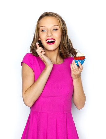 cupcakes: people, holidays, party, junk food and celebration concept - happy young woman or teen girl in pink dress with birthday cupcake Stock Photo