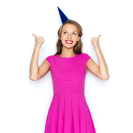 posing  agree: people, holidays and celebration concept - happy young woman or teen girl in pink dress and party cap