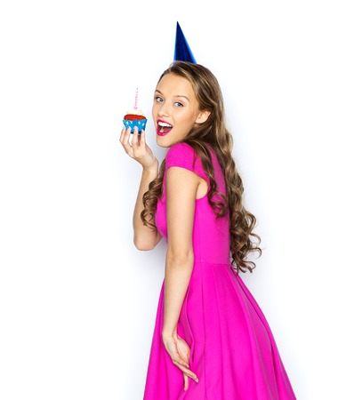 woman surprise: people, holidays and celebration concept - happy young woman or teen girl in pink dress and party cap with birthday cupcake