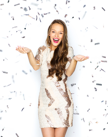 young people party: people, holidays, emotion and glamour concept - happy young woman or teen girl in fancy dress with sequins and confetti at party Stock Photo