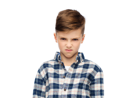 rebellious: childhood, emotion, anger, hate and people concept - angry boy in checkered shirt