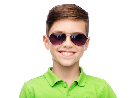 pre teen boys: childhood, fashion, accessory, style and people concept - happy smiling boy in sunglasses and green polo t-shirt Stock Photo