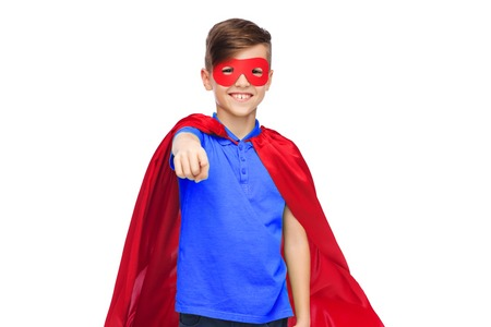 child finger: childhood, gesture, carnival costume and people concept - happy boy in red superhero cape and mask pointing finger to you Stock Photo