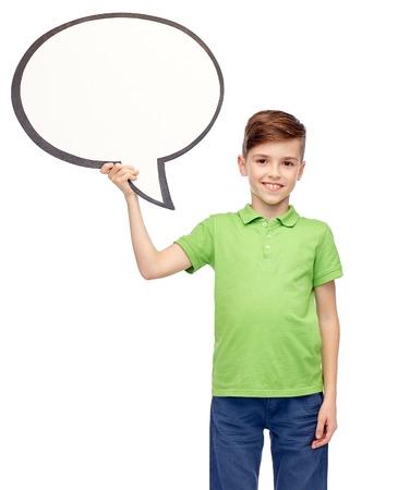 niños platicando: la infancia, la comunicación, la publicidad y el concepto de la gente - feliz niño sonriente en el polo camiseta verde que sostiene la bandera blanca de la burbuja de texto